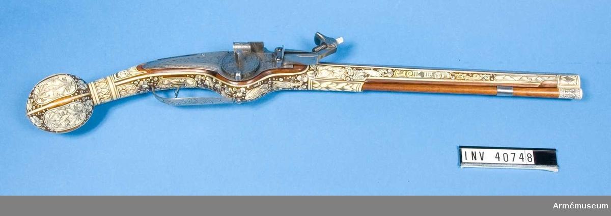 """Grupp. E:III. Hjullåspistol från 1600-talets början.  Pistolen är lika och i par med AM.040747. Pipan har sannolikt tillhört en annan pistol men är ändrad att passa i par med föregående. Knappen på kolvkulan saknas.   Enl. Arne Hoff """"Låsen efterdekorerade och stocken sannolikt förfalskad"""" /1965."""