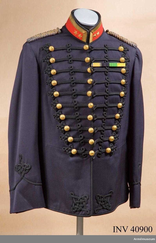 Grupp C I. Ur uniform för officer vid Smålands artilleriregemente. Består av attila, ordensband, långbyxor, ridbyxor, skärp, mössa, käppi, pompong, plym.