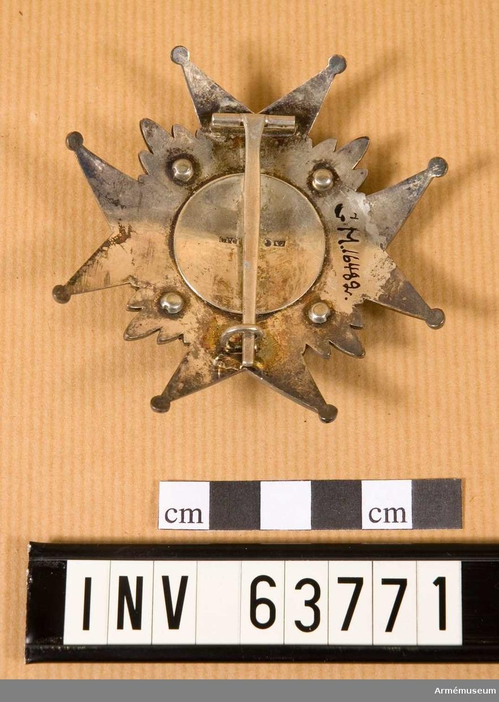 Grupp M II. Annat nr GMM 16.482. Ett johannitkors av silver med kluvna armar, varje udd slutande i en kula. Armarna är närmast korsets mitt belagda med fjäll, som utåt begränsas av utefter armarnas ytterlinjer löpande starkt strierade ränder. Mellan armarna en öppen krona i guld med tre utskjutande spetsar. På mittgloben, omgiven av en rikt ornerad gyllene bladkrans, är fältet turkosblått, därpå är lagt ett gyllene svärd med fästet nedåt och omgivet av Sveriges tre kronor.