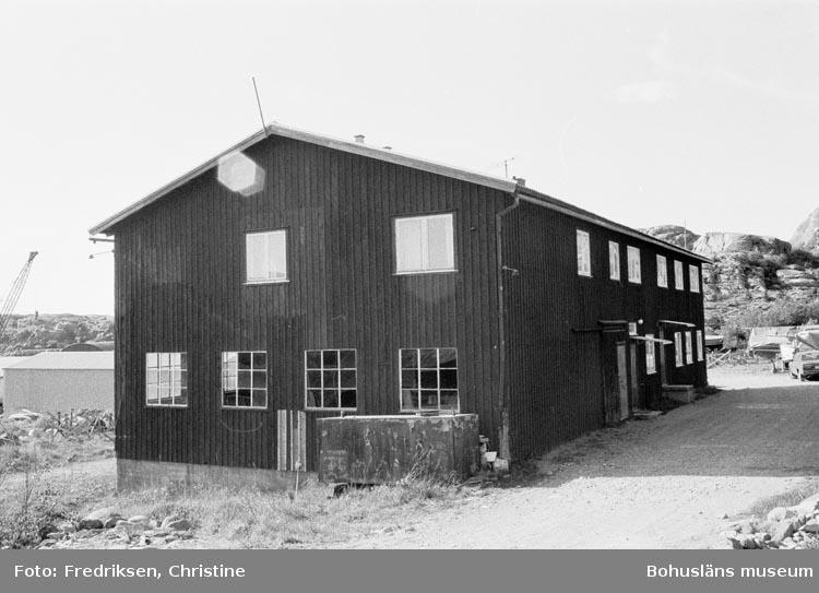"""Motivbeskrivning: """"198005. Bovallstrands Varv & Mekaniska Verkstad, Strömstad. Fiskebåt på slipen och där bakom snickarverkstaden (reparations och nybyggnadsvarv under åreb1946 - 1962).""""."""