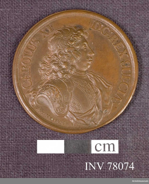 Grupp: M. Åtsidan: CAROLUS XI D.G. REX. SUECIÆ. Bröstbilden åt höger i praktfullt harnesk samt snett över bröstet och venstra axeln mantelveck, som sluta bak om ryggen - Nedanför: ANT. MEYBVSCH FEC.  Frånsidan: A COELO EST QUAE DAT PACEM. En hand ur skyn lägger en palmkvist och en lagerkrans på en kunglig krona, som står på en kub med inskrift å framsidan: CONSTANTIA VICTRIX 1679. Omkring ligga brutna vapen och fanor samt kanoner, ur vilka skotten gå ut, men böja sig tillbaka. Överst ett strålande JHVH (med hebreiska bokstäver).