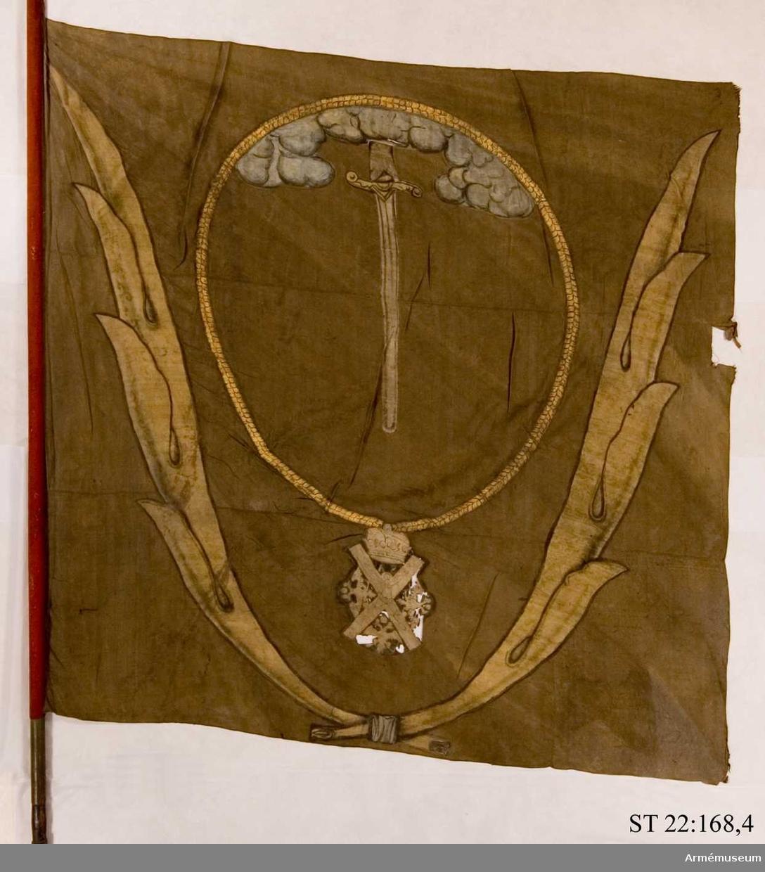 """Duk av brun kinesisk sidendamast. Dekor i intarsia och målade detaljer. Motivet föreställer en hand med svärd som kommer ner ur ett moln omgivet av andreasordens kedja med dess insignier nedtill. Det hela omgivet av nedtill korslagda palmkvistar. Grönmålad, slät stång. Urtaget """"handtag"""", nedanför detta är stången kantig och rödmålad. Stången avkortad. Spetsen avbruten."""