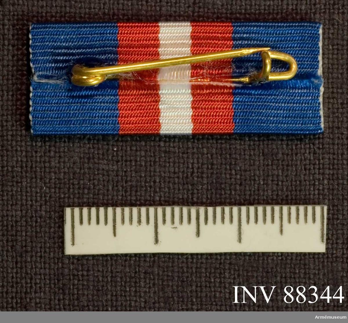 Släpspänne till okänd utmärkelse Blått band kluvet i rött och vitt.