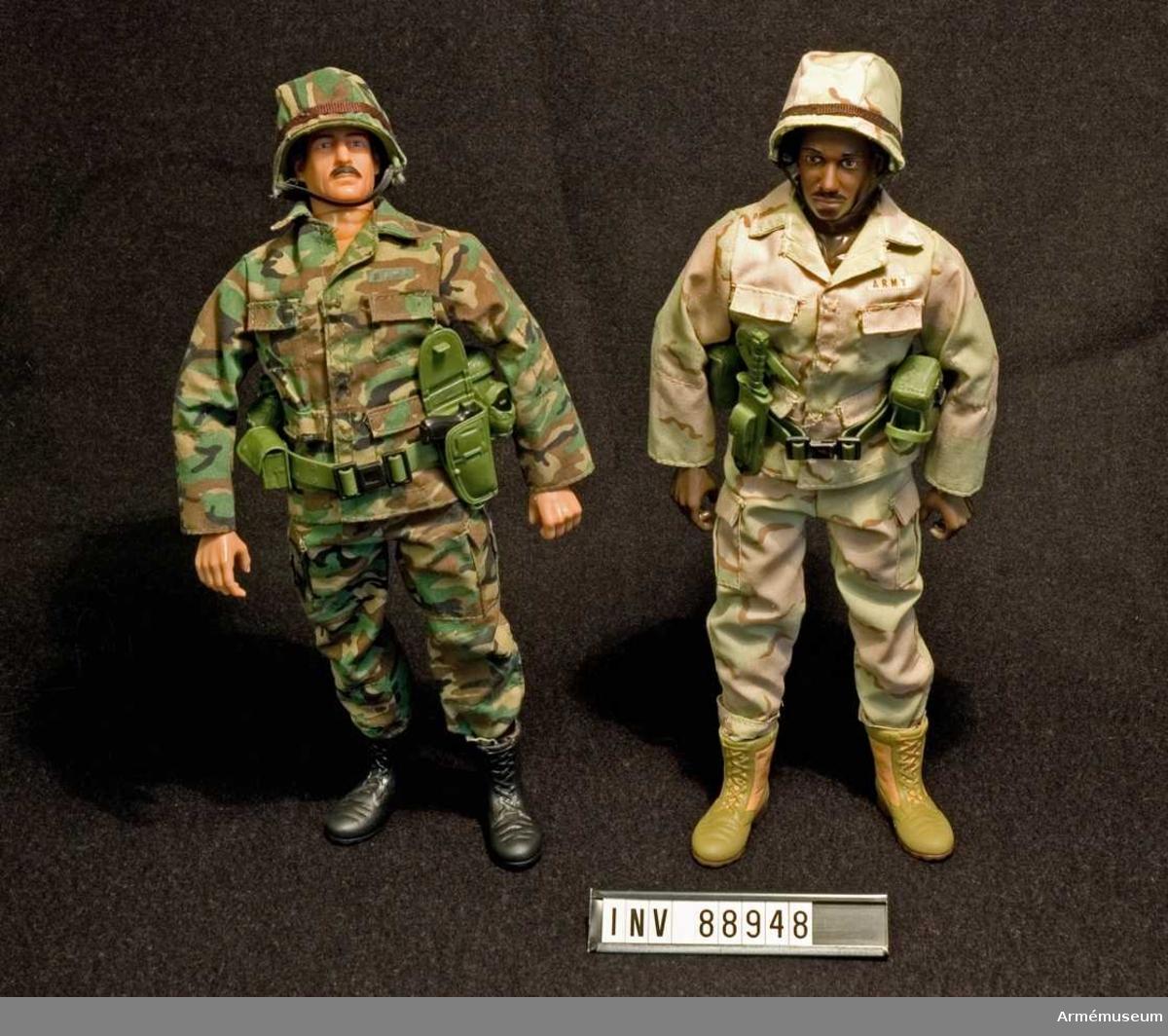 """Två stycken dockor med tillbehör.  Docka 1: Komplett uniform i skogskamouflage, med tillhörande kängor och hjälm. På uniformen finns ordet """"ARMY"""" tryckt. Kring midjan ett bälte med två väskor, automatpistol i hölster och vattenflaska.  Docka 2: Komplett uniform i ökenkamouflage, med tillhörande kängor och hjälm. På uniformen finns ordet """"ARMY"""" tryckt. Kring midjan bälte med två väskor, kniv i slida och vattenflaska."""