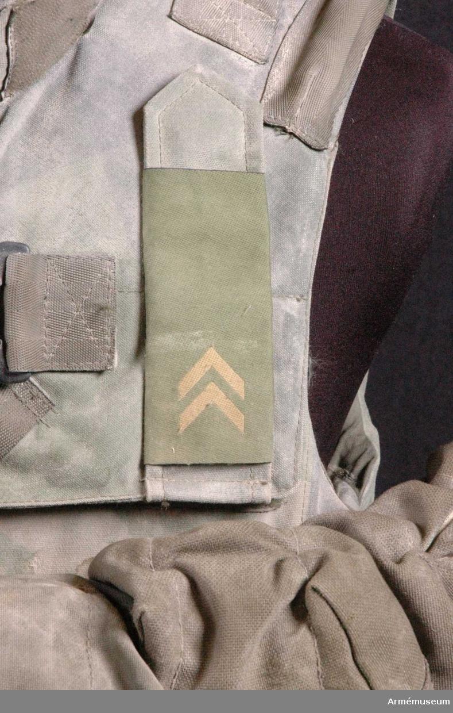 Storlek: Small. Tillverkad i Rumänien. På vänster bröst sitter gradbeteckning för kadett. Sex stycken väskor sitter i midjehöjd och på ryggen en vattenbehållare (AM.096017) med slang fastsatt med ståltråd samt två karbinhakar. En kniv (AM.096018) är instucken bakom en av väskorna. I väskan längst till höger ligger en enkelkikare, en kompass fyra ljusstavar (två röda, två gröna). (AM.096008-AM.096010) I väska nummer två från höger ligger två par handskar och ett magasin till AK 5. (AM.096011-AM.096013) I väska nummer fyra från höger ligger ett par solglasögon. (AM.096014) I den undre väskan ligger en rulle svart eltejp och ett fodral med två öronproppar. (AM.096015-AM.096016)