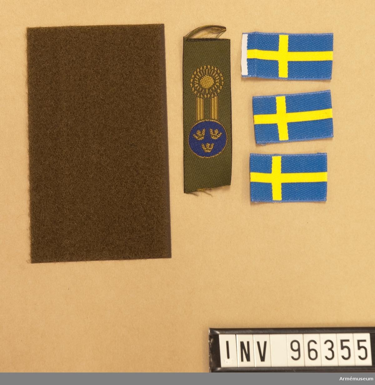 Tre nationalitetsmärken, ett mössmärke samt en kardborrelapp.