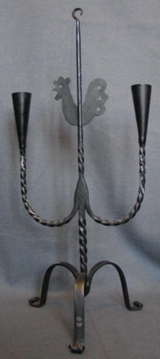Trebent ljusstake med två spetsiga ljushållare. Ten i mitten med tupp.