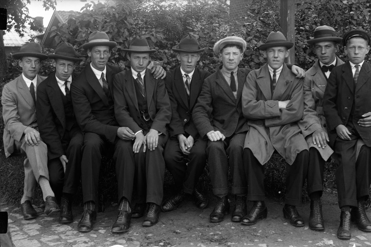 Åtta män och en pojke sitter framför en häck. Gustav Andersson (4).
