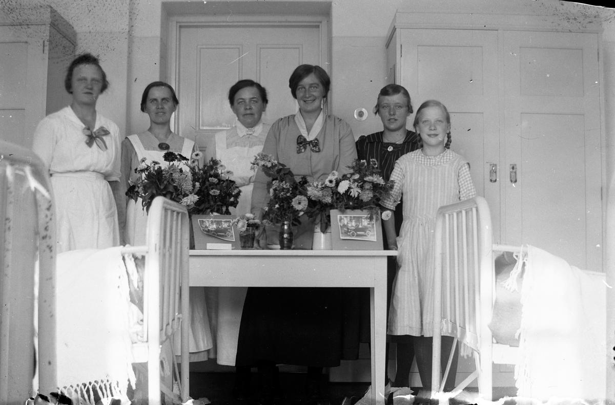 """Fem kvinnor och en flicka står vid ett bord med blomvaser på, i bakgrunden syns två skåp med dörr och i förgrunden två sjukhussängar, på Lungkliniken i Eksjö. Fotografens anmärkning: """"Gruppbild på sexan b""""."""