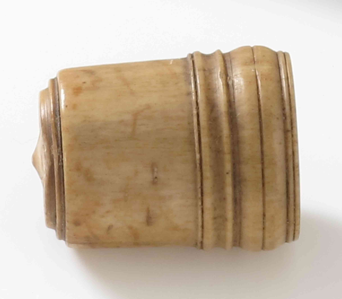 Lokk til nålehus (?)  eller annen sylinder.  Elfenben.  Av form som et litt stort fingerbøl,  med innvendige skrugjenger,  utvendig profilringer nederst og rundt  toppflaten, som har en liten midtknopp,  Innrisset rundt midtknoppen:   PMK  =lettmatros Peder Madsen.
