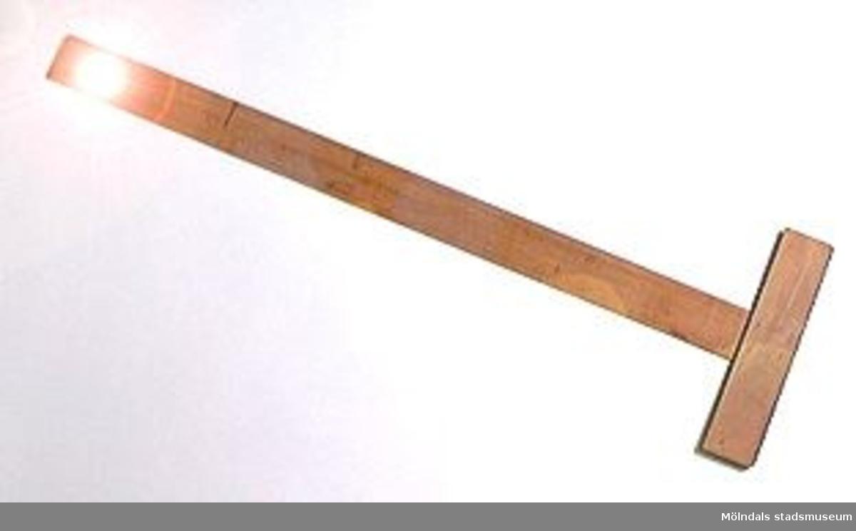 En så kallad T-linjal av trä, som använts vid möbelsnickeri.Litteratur: Red. Särnstedt Bo, Lindome Västsvenskt möbelsnickeri under 300 år, Stockholm 1977. Utställningskatalog från Liljevalchs Konsthall 1977-06-30 - 1977-09-11. Se sid 22-23 för historik kring fam. Thorsson.Mölndals Museum Lindomemöbler, Länstryckeriet Göteborg 1994. Utställningskatalog innehållande kapitel rörande familjen Thorssons verksamhet.