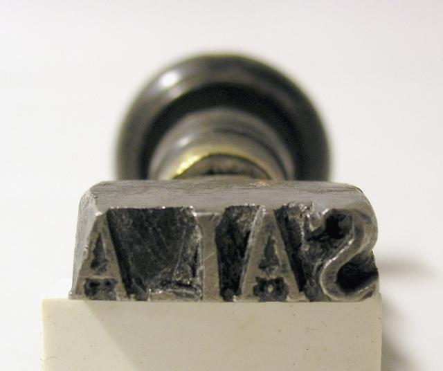Stämpel, med stamp av stål, träskaft med mässingsring. Avrakstämpeltyp utan ram. Avtryckets mått:31x9 mm.
