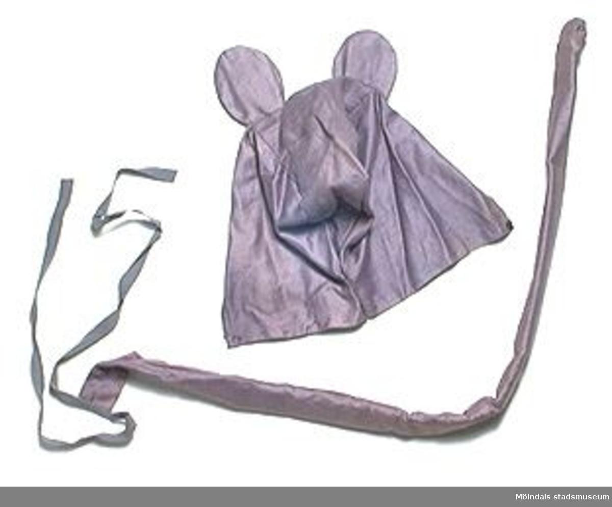 Musöron med svansar. 3 huvor med musöron avsedd för barnhuvud. 3 svansar: L 810 mm ca. Musöronen sitter på en huva som knäpps under hakan. Svansarna består av ett sytt tygrör, som har stoppats upp med papper.
