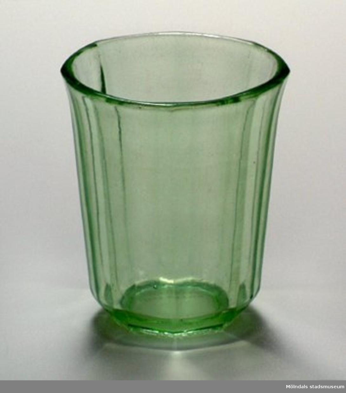 Grönt, åttakantigt glas, vidare upptill än nertill.Ägarna är givarens föräldrar.