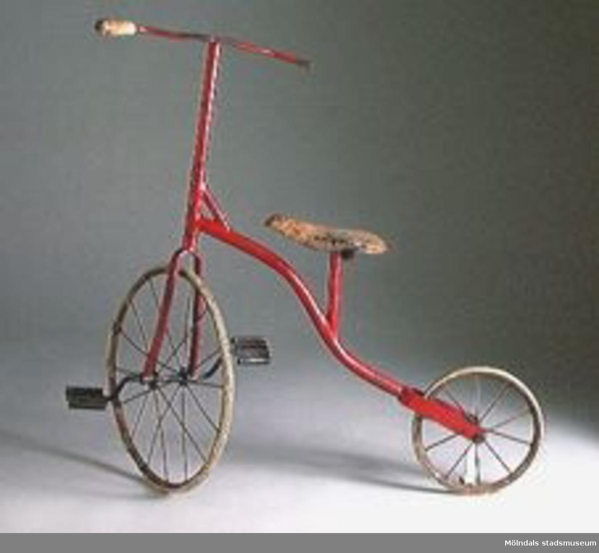 Gammal barncykel av järn med däck av massivt gummi. Handtag av trä. Trampor på framhjulet. Rödmålad. Färgen repad, gummit på hjulen håller på att falla av. Ena handtaget saknas.Tidigare sakord: barncykel.Upphittad på Kikåstippen 1985 av givaren.