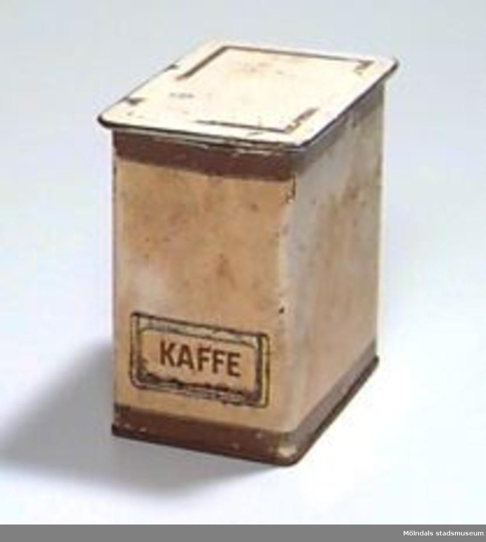 """Rektangulär, beige burk med lock. Dekorränder i brunt och guld upptill och nertill på burken, samt på locket. På ena kortsidan står """"KAFFE"""" i brunt. Runt texten finns en ram av metall, så att man kan ange annat innehåll genom att placera en etikett i ramen.Ägarens adress (Ort) kan även benämnas Forsåkersg. 10.Givare även: Wågdahl, Ann-Kristin, Sagbrov. 37, Lindome.Rostig, sliten och mycket fläckig."""