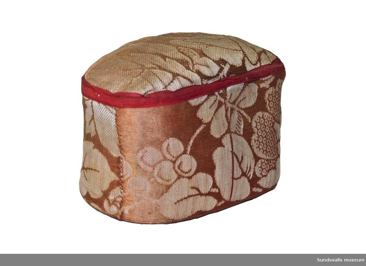 Föremål klätt med rosa jacquardvävt tyg, röd bandkant och mörkblått filttyg i botten. Föremålet är fyllt med något mycket tungt material. Funktion som brevpress?