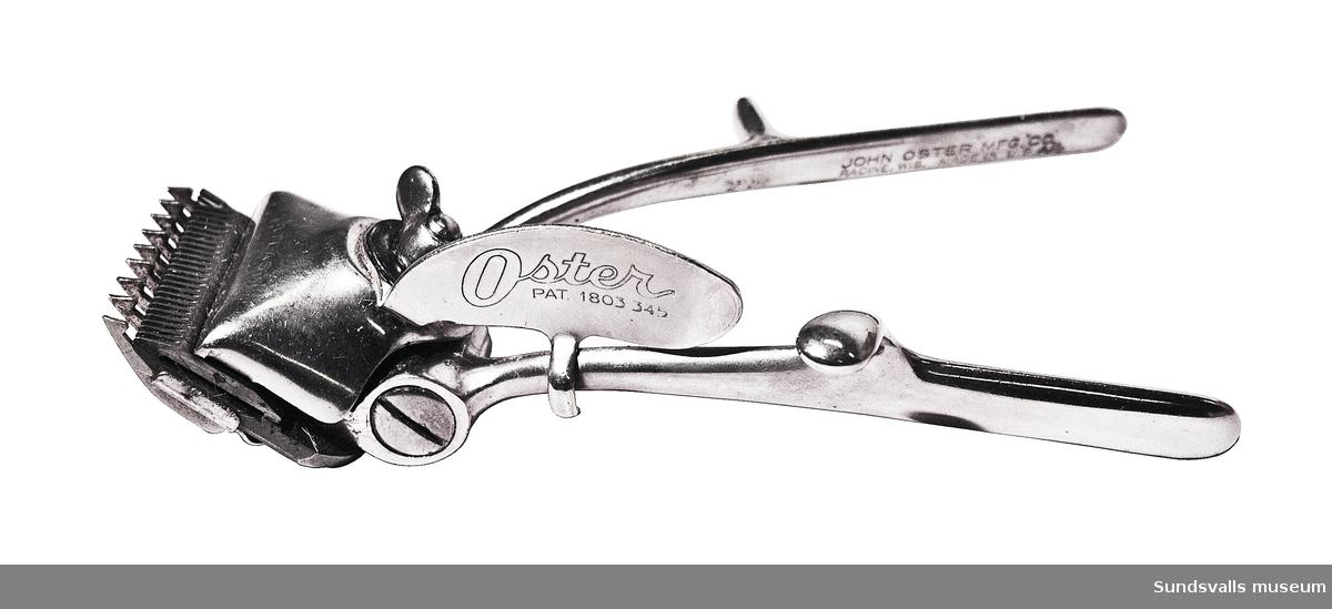 Trimmer, frisörtillbehör. Instrument att klippa hår med. Två handtag med tum- och fingergrepp. Framtill finns en vingmutter att ställa in önskad klipplängd med. Modellnamn 'Atlas', samt stämplad med tillverkarens namn och 'Oster PAT. 1803 345'. Förvarades tidigare inuti SuM 3452. Användes av givarens far, Hjalmar Pettersson, som levde 1896-1978.