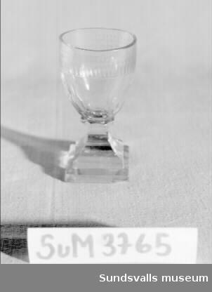 Glas för vin. Ovoid, äggformad, kupa med olivslipning på den nedre delen och en graverad bård kring kanten med ett stiliserat växtmotiv. Glaset står på ett fyrsidigt slipat ben med en kvadratisk, slipad fot. Enligt givaren en gåva till försäkringstjänstemannen Hjalmar Hamrin i samband med hans värderingsarbete efter branden i Sundsvall 1888. Glasets skeva mynning och kantstötthet ska vara en brandskada. Litt.: Carl F. Hermelin, Elsebeth Welander, Glasboken - historia, teknik och form (Askild&Kärnekull, Borås 1980).