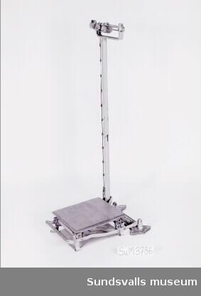 Personvåg i metall med en träplatta att stå på för den som skulle vägas. Typnamn STATHMOS FOX. Vågen användes på den år 1875 invigda 'Lindgrenska Arbetsinrättningen', sedemera pensionärshemmet Holmgården, Sundsvall.