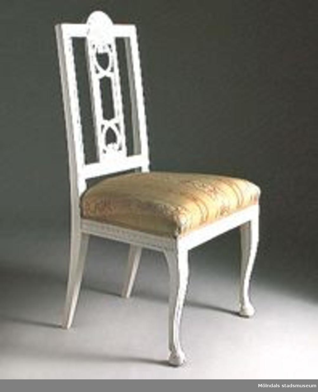 """Stol, sengustaviansk, med s.k. """"Gunnebobricka"""" i ryggen. Solfjädersornament på krön och bladsnitt i rygg och sarg. Frambenen med fotavslutningar i form av skurna bockhovar. Stolen har ursprungligen varit målad i en brunröd nyans. Vitmålad på 1900-talet.Halva stolen med framtagen originalfärg. Stolen är osignerad men är sannolikt tillverkad i Lindome omkring år 1800. Ryggbrickans genombrutna utformning återgår på en ritning av Carl Wilhelm Carlberg för en stol Gunnebo, därav namnet """"Gunnebobricka"""". Denna stol en utomordentligt hög kvalitet i skärningarna och benens utformning. Troligen är stolen del av ett större möblemang och utfört som en specialbeställning.Inköpt från antikhandeln Stopalo, Stockholm."""