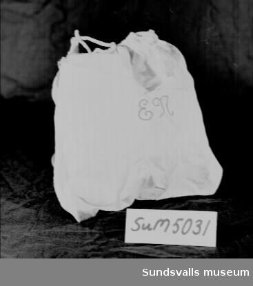 Slöjdväska i ljusblå- och vitrandigt bomullstyg med dragsko. Ett broderat monogram i rött mitt på, 'EN'. Givaren har fått väskan efter sin mor, Ella Pettersson, född Näsholm 1901 i Dockmyr. Hon flyttade till Sundsvall 1926 och gifte sig med Hjalmar Pettersson (f 1896 d 1978) 1928. De bosatte sig i Gustavsberg på Alnö.
