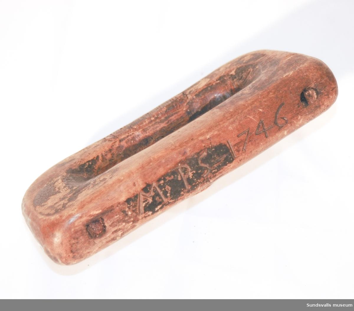 Redskap, eventuellt för läder- eller skinnberedning, utformat som ett hantag med en bågformad slipad 'kniv' framtill. Märkning skuren i träet 'MPS 1746'. Enligt anteckning kommer redskapet kanske från Stöde.