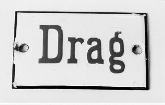 """Skylt, rektangulär, tillverkad i emaljerad järnplåt. Blå text""""DRAG"""" på vit botten. Svart ram kring kanterna. På kortsidorna finnshål för fastsättning av skylten. Skylten hittades på Postmuseums vindav en museitjänsteman."""
