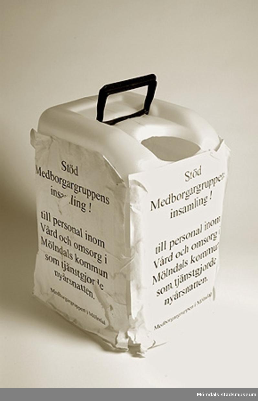 """Vit plastbehållare användes som insamlingsburk av Medborgargruppen i Mölndal.Påklistrad text: """"Stöd Medborgargruppens insamling till personal inom Vård och omsorg i Mölndals kommun som tjänstgjorde nyårsnatten."""" 2000."""