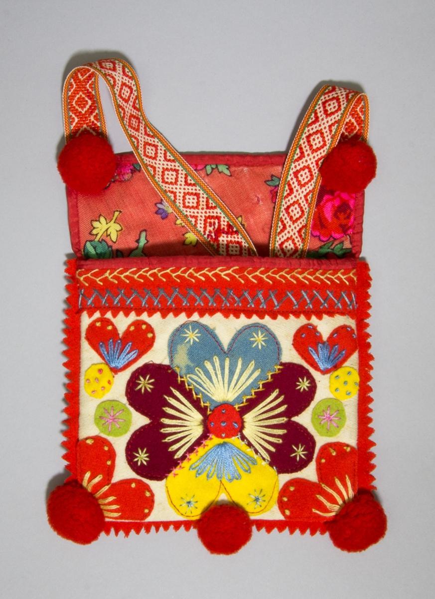 Kjolsäck inspirerad av dräkt för kvinna från Rättviks socken, Dalarna. Modell med avskuret framsstycke. Tillverkad av vitt fabriksvävt bomullstyg, med applikationer av ylletyg, kläde, i rött, mörkrött, gult, blått och grönt, fastsydda med maskinsöm. Centralt placerad hjärtblomma omgiven av mindre hjärtan och rundlar. Broderi utfört med glansigt bomullsgarn, moulinégarn, i flera färger: flätsöm, sticksöm, öglestygn och knutsöm. Ovanför applikationen en remsa rött kläde, uddklippt i nederkanten, med flätsöm och kråkspark. Kantning upptill med rött konstsilkeband. Inlägg av en remsa rött kläde i sido- och bottensömmen. I nederkanten fäst tre runda bollar av rött ullgarn. Överstycke av yllemuslin med tryck i flera färger på röd botten. Foder av fabriksvävt bomullstyg, vitt med litet tryck i rött. Bakstycke av mörkblått kläde. Axel- eller midjeband handvävt, med plockat mönster av rött ullgarn på vit botten. Vid bandets fäste på kjolsäcken sitter två ullbollar av rött ullganr.