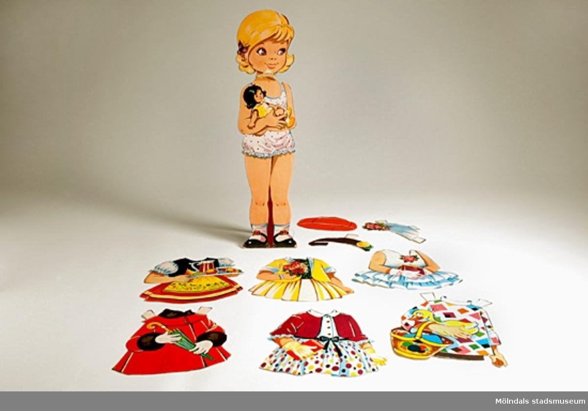 Blond flicka med docka i handen i rosa underkläder.6 st. klädesplagg, 3 st. hattar.