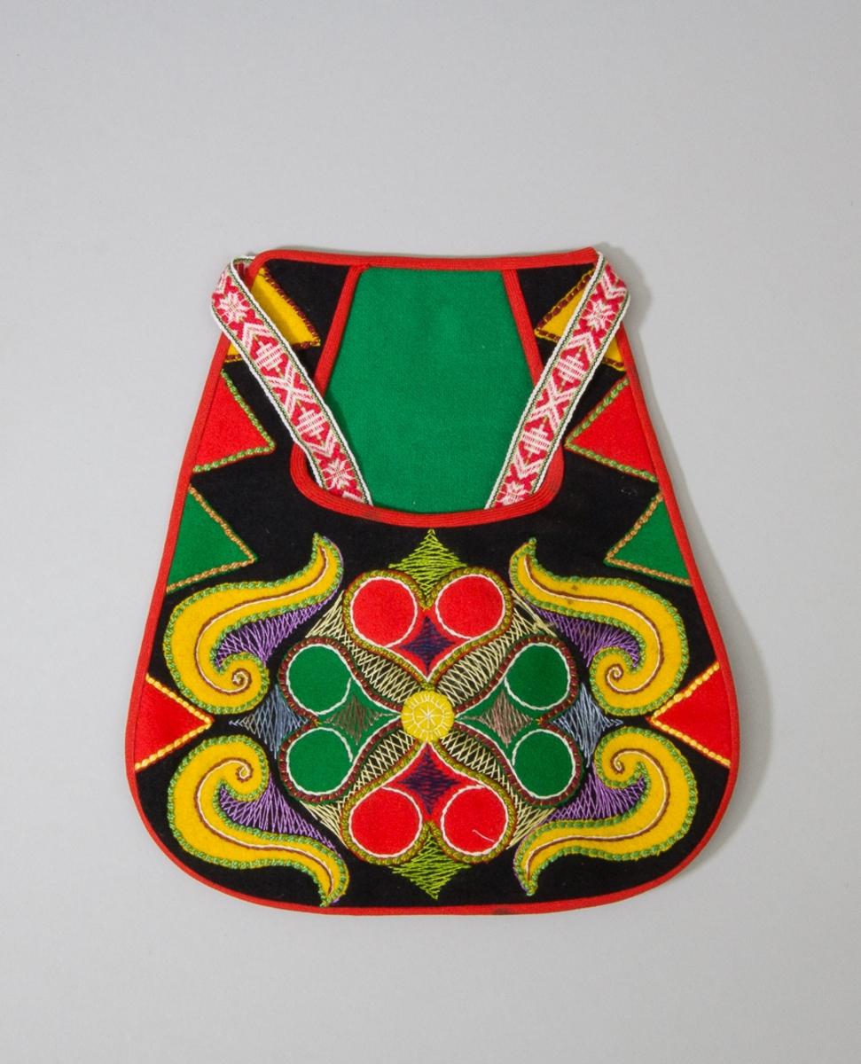 Kjolsäck till dräkt för kvinna från Leksands socken, Dalarna. Modell med u-formad öppning. Tillverkad av svart ylletyg, kläde, med applikationer av rött, grönt och gult kläde, fastsytt med läggsöm i olika färger, pärlgarn. Centralt placerat hjärtmotiv omgivet av slingor, trekanter längs kanten. Broderi runt mittmotivet sytt med en tråd blankt garn, troligen sysilke i olika färger: flätsöm. Foder till framstycket av fabriksvävt bomullstyg med tryckta ränder i brunt, orange och vitt. Kantning runtom gjord med diagonalvävt band av ull. Grönt kläde i öppningens spegel. Bakstycke av svart kläde. Midjeband fabriksvävda med plockat mönster i rött på vit botten, bomull.