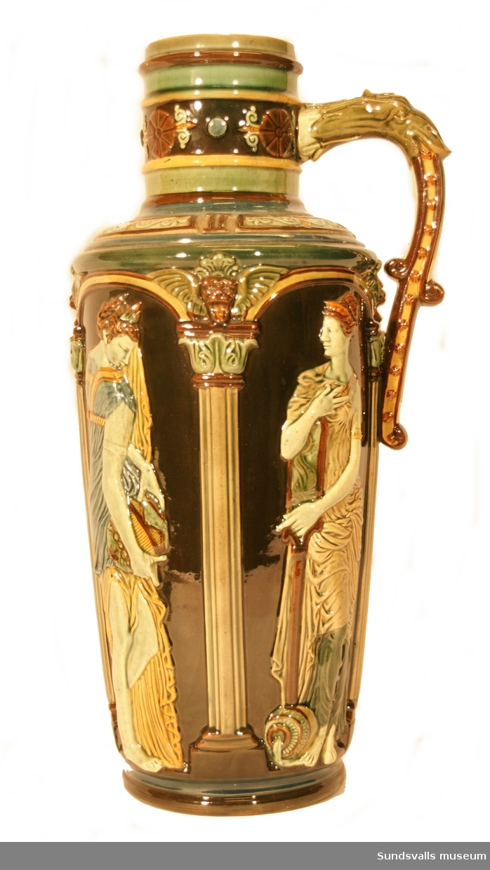 Krus i lergods med majolikaglasyr i blått, grönt, vitt och gult. Gjuten dekor föreställande kvinnofigurer i klassicistisk dräkt, bärande vatten- eller vinkrus. På hänkeln finns ett drakhuvud.