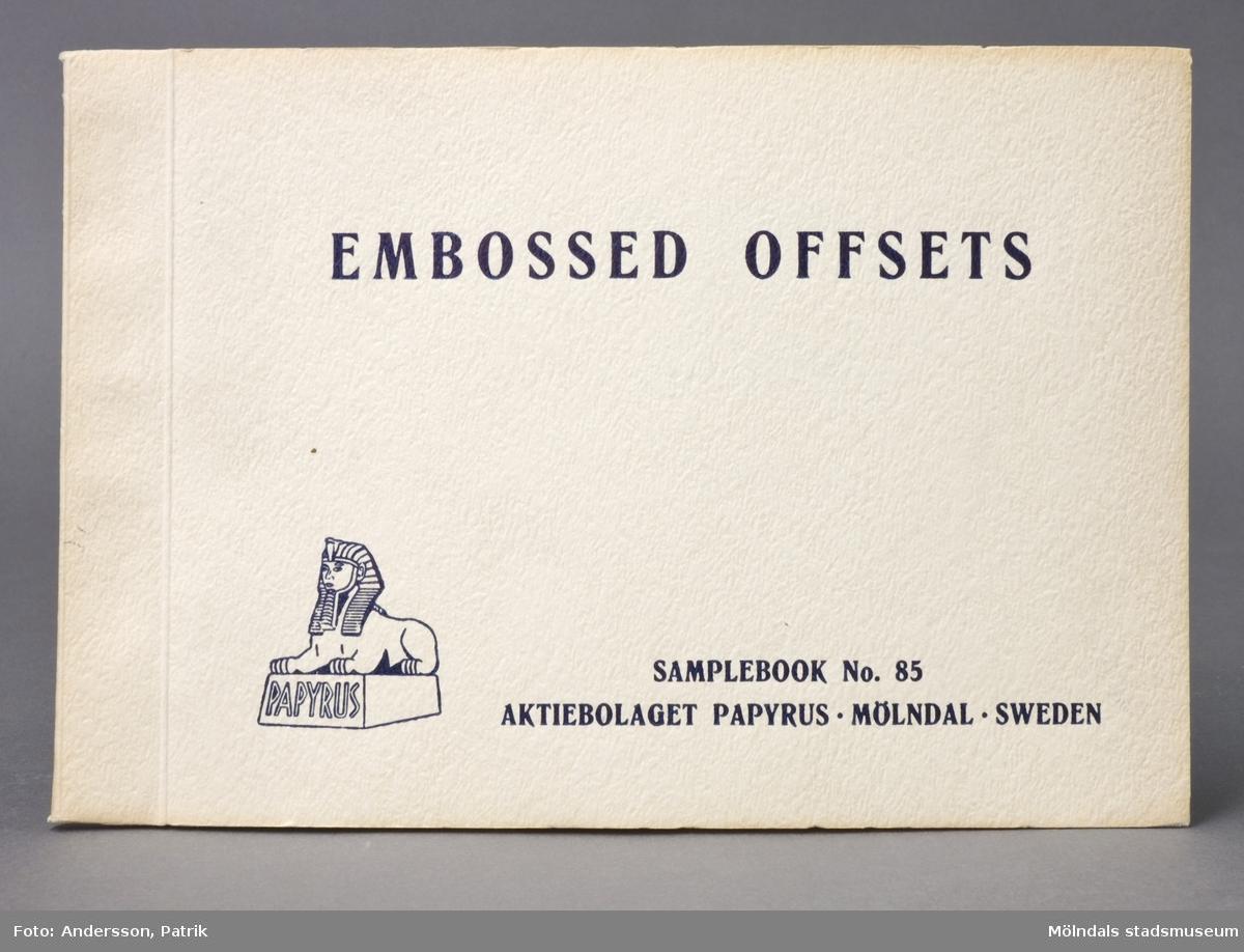 """Provbok No 85. Häfte med mönsterpressat papper. Logotyp med sfinx på fundament. Pärm av gult mönsterpressat papper, med svart relieftryck; """"Embossed Offsets"""". Produktinformation på engelska. Provarken är märkta med bokstäver. Litteratur: Papyrus 1895-1945, Minnesskrifter, Esseltes Göteborgsindustrier AB, Göteborg 1945."""