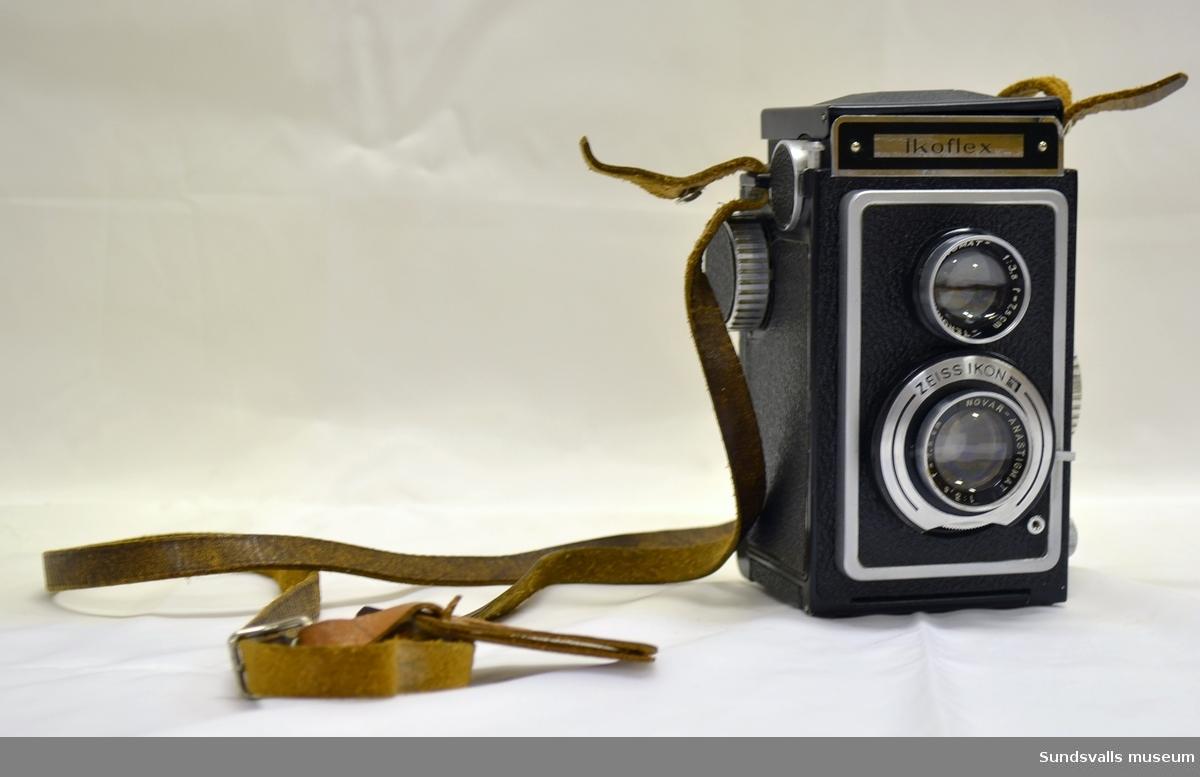 Svart kamera i metall, glas och plast med modellnamnet Iko Flex, från producenten Zeiss Ikon. Fastmonterad bärräm i brunt läder, varpå tidigare ägares namn står uppgivet.