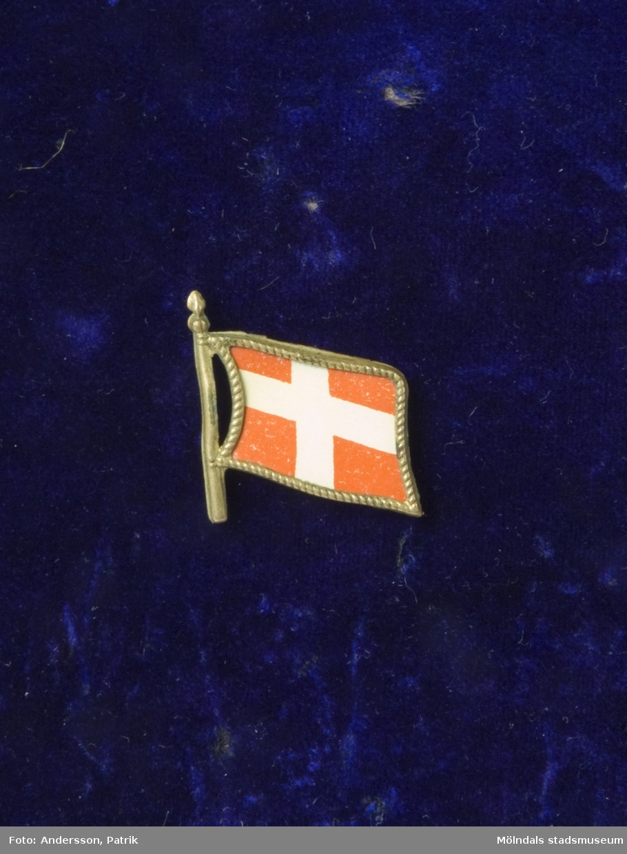 Minnesnål ägd av tungviktsboxare Henry Nicklasson. Märke av metall och plast, föreställande danska flaggan. Nål för fastsättning på baksidan.