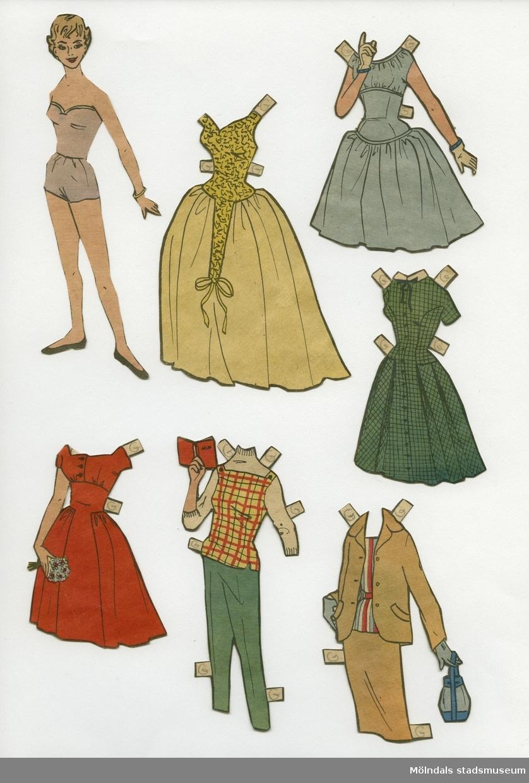 """Klippdocka med kläder och tillbehör, urklippta ur tidning på 1950-talet. Docka och kläder märkta """"Gunilla"""" på baksidan - dockans namn. Dockan föreställer en ung kvinna, tecknad, med blont hår i kort frisyr, iklädd underkläder (topp och underbyxor).Garderoben består av tre kortare klänningar, en längre klänning, set med byxa, polotröja och väst, dräkt med kavaj, skjorta och kjol, kappa med paraply, lucialinne med krona och stjärngosse, samt två skiddräkter (jacka med kapuschong och byxor), varav en med skidor och en med stavar."""