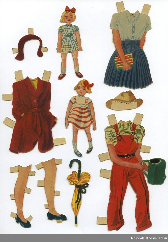 """Pappdocka med kläder och tillbehör från 1950-talet. Docka och kläder är märkta """"Lisa"""" på baksidan - dockans namn. Dockan föreställer en flicka med rött hår, iklädd underkläder, strumpor och skor. Garderoben består av två klänningar, två set med blus och kjol, soldräkt, hängselbyxor, kappa, skor och strumpor, samt fyra huvudbonader. Hon har också tillbehör, såsom egna dockor, ett paraply och en rund skylt med dockans namn.Docka med kläder och tilllbehör förvaras i ett ihopvikt, grönrandigt papper, tillsammans med annan pappdocka (MM 04674)."""