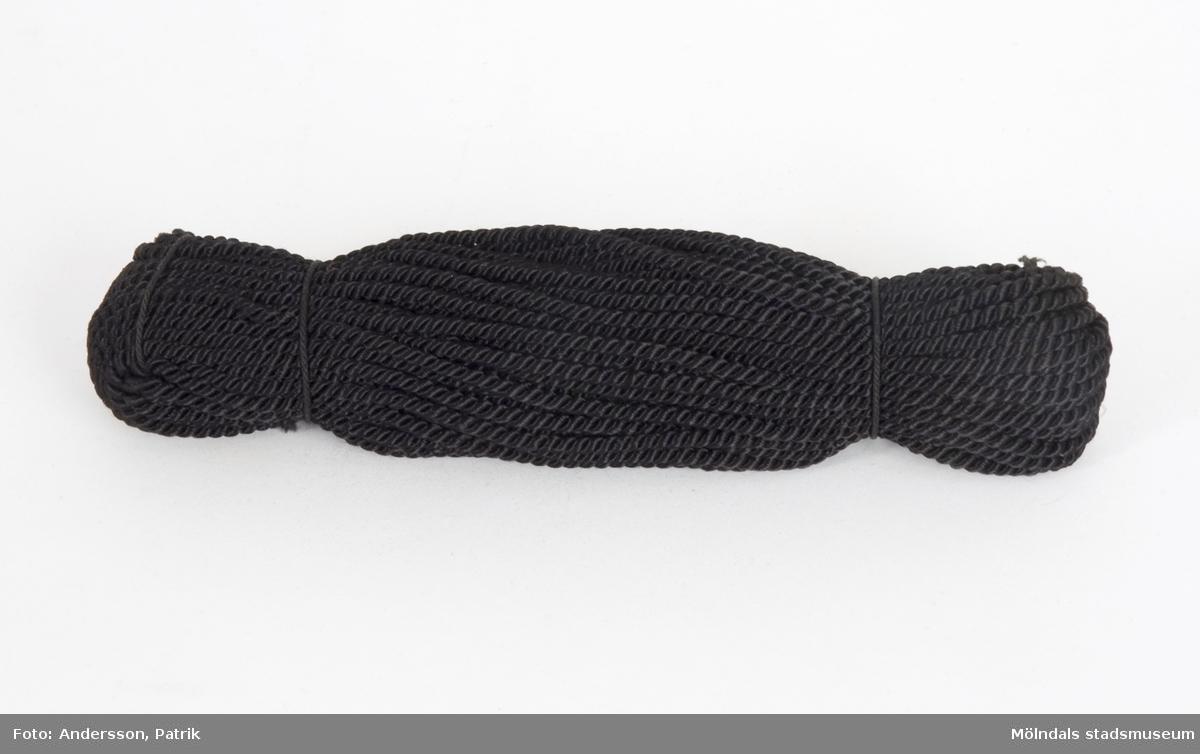 Silkesnöre, tvinnat, svart i garndocka. Snöret användes för bokbindning på Papyrus, på Kuverteringen.
