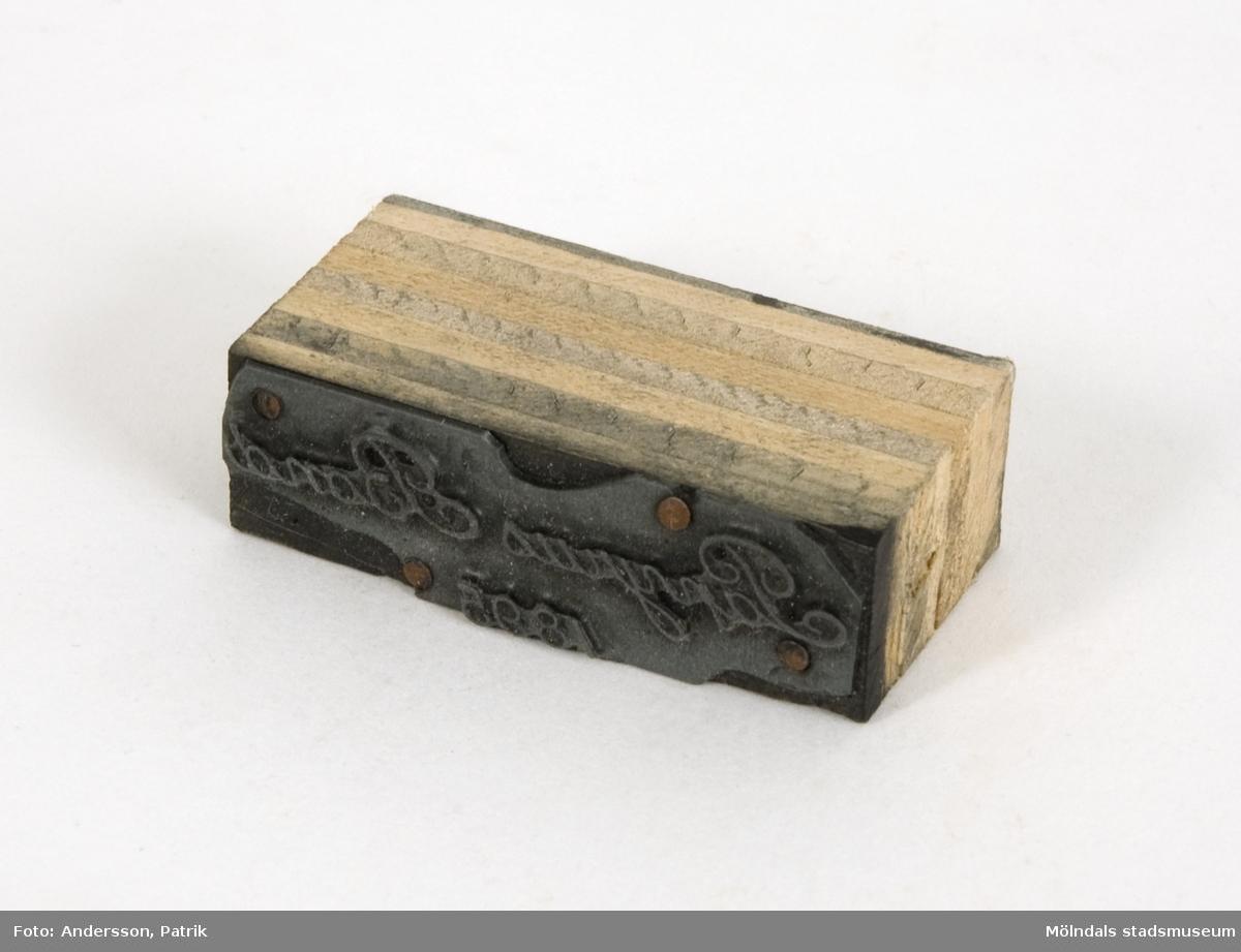 """Trycktyp av metall, monterad på träkloss, från Papyrus. Texten på typen: """"Papyrus Bond 1895"""". Motivet är spegelvänt för att det skall överföras rättvänt vid tryck på papper."""