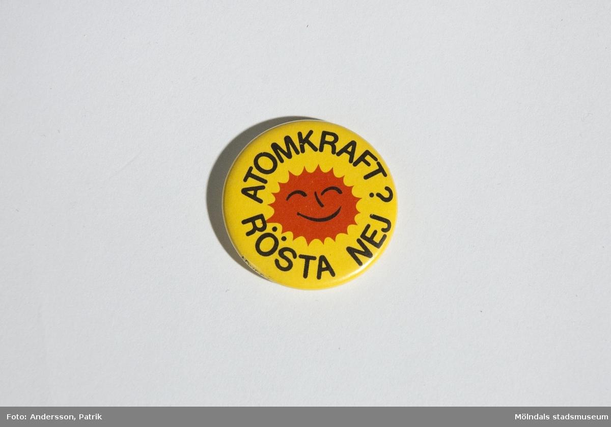 """Pinn med symbolen och texten: """"ATOMKRAFT? RÖSTA NEJ"""".Den har gul bakgrund, symbolen är röd och texten är svart.Denna användes av Lena Måvholm 1979 i samband med  folkomröstningen om kärnkraft i Sverige som skedde 1980.MåttDiam: ca. 38 mm1980 skedde en folkomröstning om kärnkraften i Sverige. Då var det många personersom under 1970 och 80-talet bar på denna symbol. Antikärnkraftsymbolen liknade ett glatt rött/orange eldklot och hade texten: """"ATOMKRAFT? NEJ TACK"""". Det var en livskraftig symbol som ville visa energi och framtidstro. Den ville visa vad man borde använt sig av i stället såsom solen, naturen och vinden."""