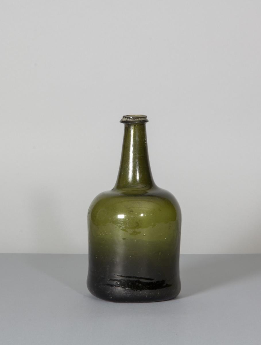 Butelj i grönt glas. Rundade sidor med förhållandevis lång, ringförsedd hals.