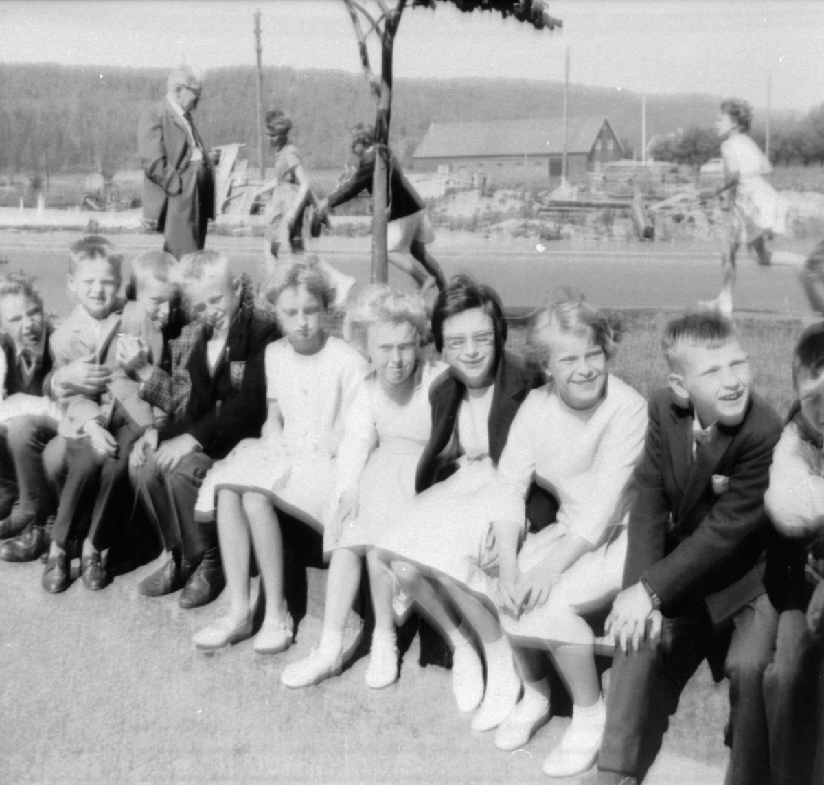 Examensklädda flickor och pojkar sittandes vid gatan. 3:e klass. Tillfällig skollokal på Hagåkersgatan.