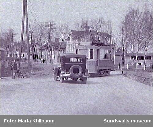 Kollision mellan bil och spårvagn. För det mesta höll sig bilarna undan spårvagnarna, men här i Kubikenborg överraskades förmodligen bilföraren av att spårvagnen svängde över landsvägen. Kollisionen var oundviklig - men dessbättre med små skador som följd. I annonser i lokaltidningarna hade Sundsvalls Spårvägs AB informerat och varnat sundsvallsborna med uppmaning som: Gå ej i spåren. Passera ej spåren, innan ni först övertygat eder att ingen vagn är i annalkande.  Håll barnen från spåren.  Onödig körning i spåren är förbjuden vid böter från 5 till 100 kronor.