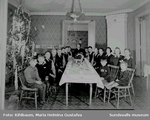 Grupporträtt. Barn och kvinnor sitter vid ett bord, julgran.