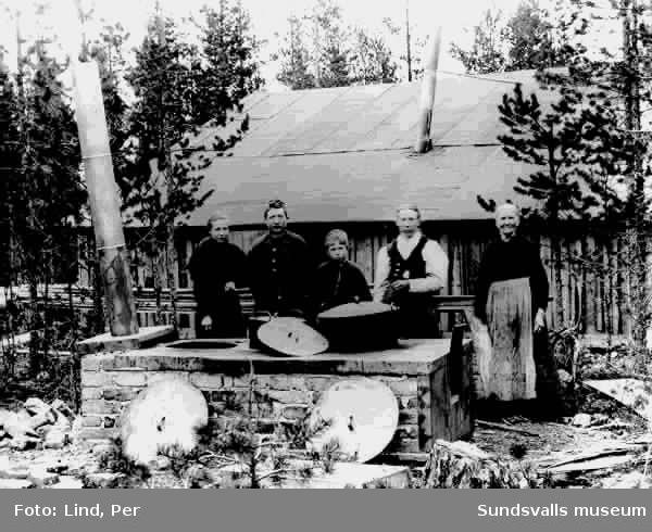 """Alby 1898. """"Ångköket"""". Gruppbild med tre vuxna och två barn som lagar mat.  Stor vedspis för utomhusbruk i bakgrunden ett trähus."""