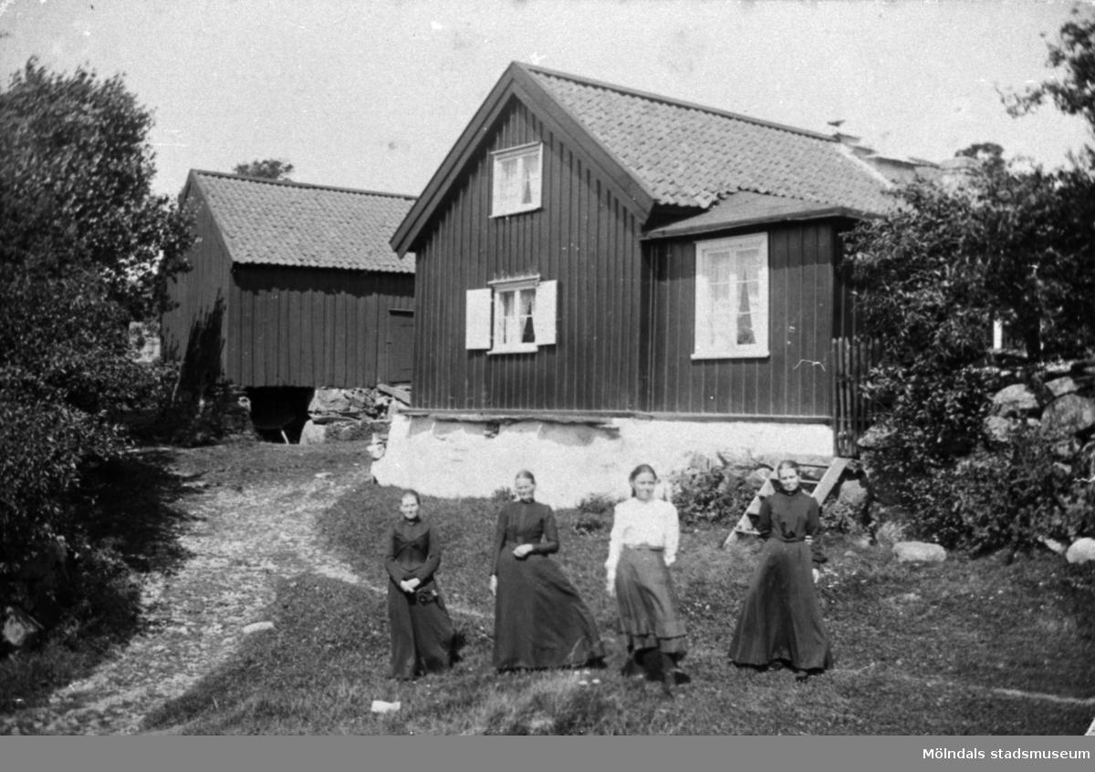 """Från v: Anna Carlsson (1872-1955), Maria Eriksson (1840-1925), Valdeborg Johansson (1891-1970) och Josefina Eriksson (1856-1928). Anna arbetade som piga i stugan.Text på baksidan av fotot: """"'Ola stugan' Vommedal Östergård"""".(Maria är syster till Josefina och moster till Valdeborg)."""