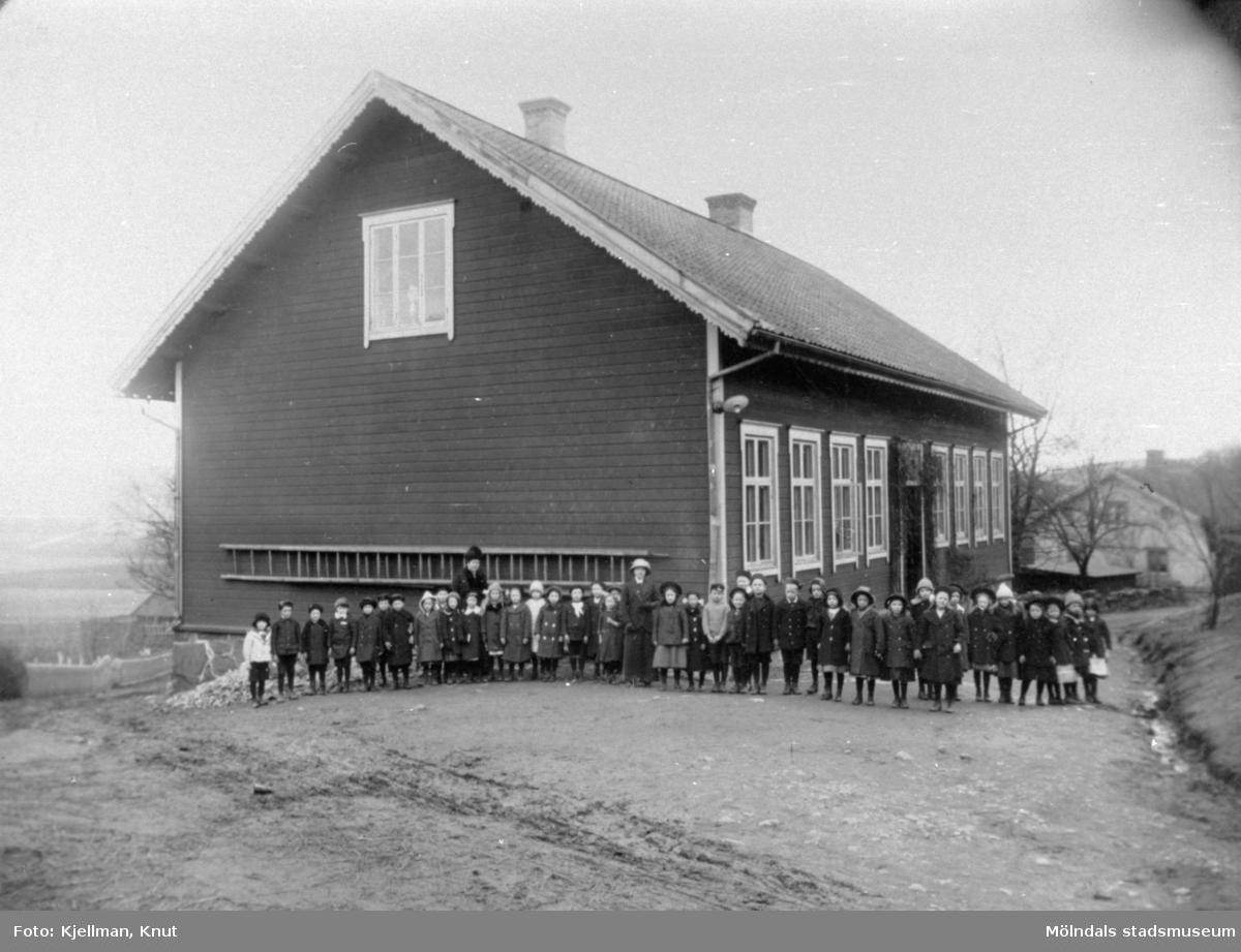 Skolklass med lärarinna uppställda utanför Holtermanska skolan, före branden 1914.