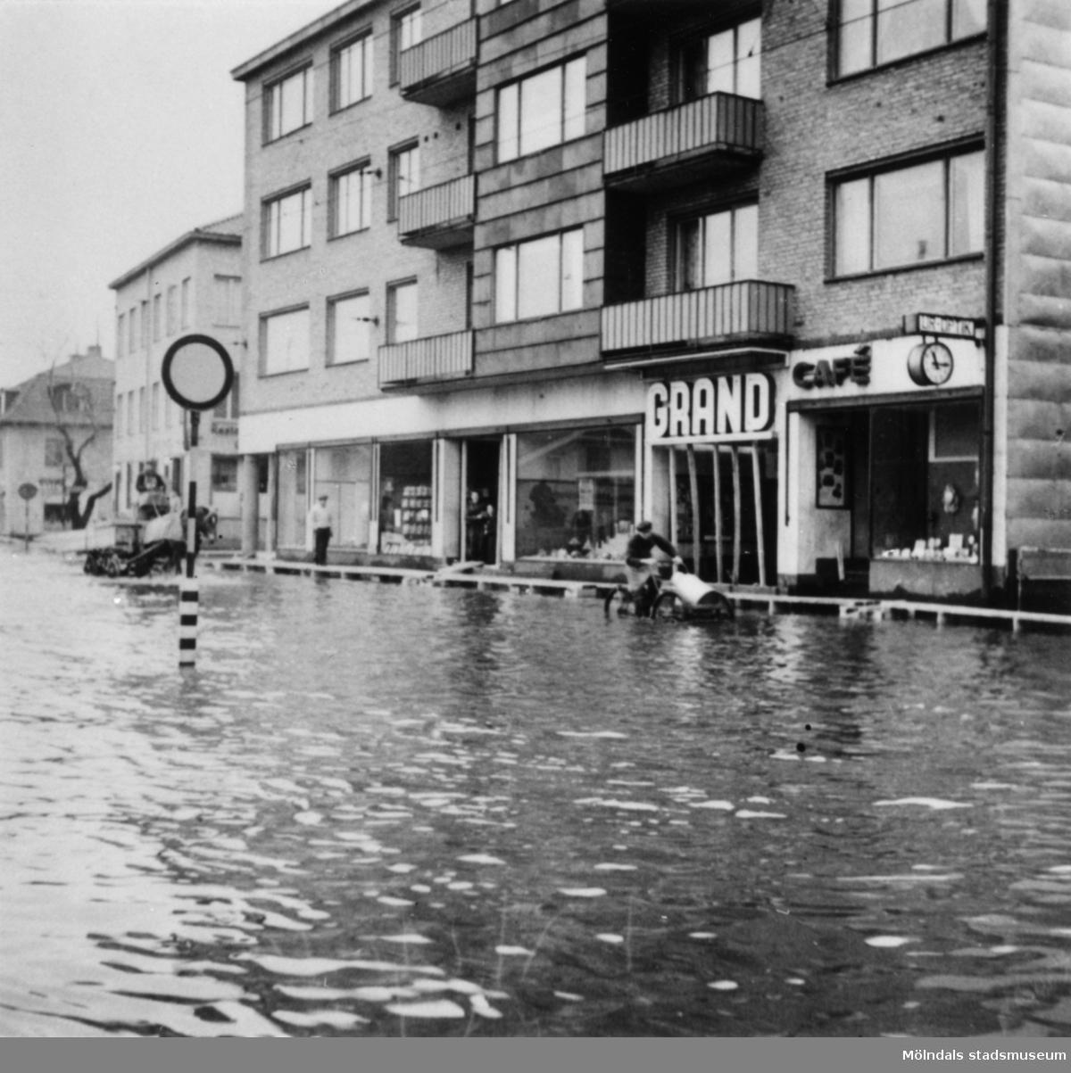 Cykelbud och hästtransport som färdas i vattenmassorna. Översvämning utanför Grand i Mölndalsbro kl 11.15 på förmiddagen. Omkring 1940.
