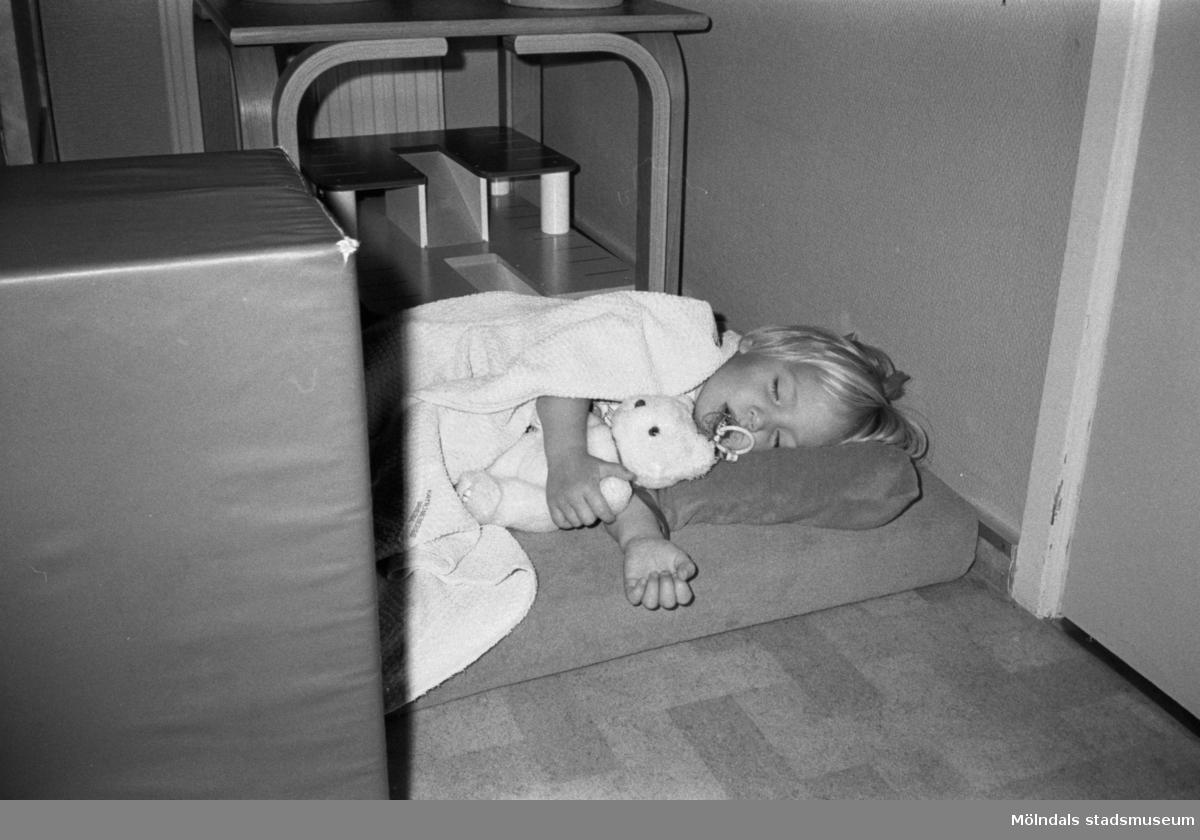 Ett litet barn med napp och nalle, ligger och sover på en kudde och madrass placerad på golvet. Katrinebergs daghem, 1992-93.